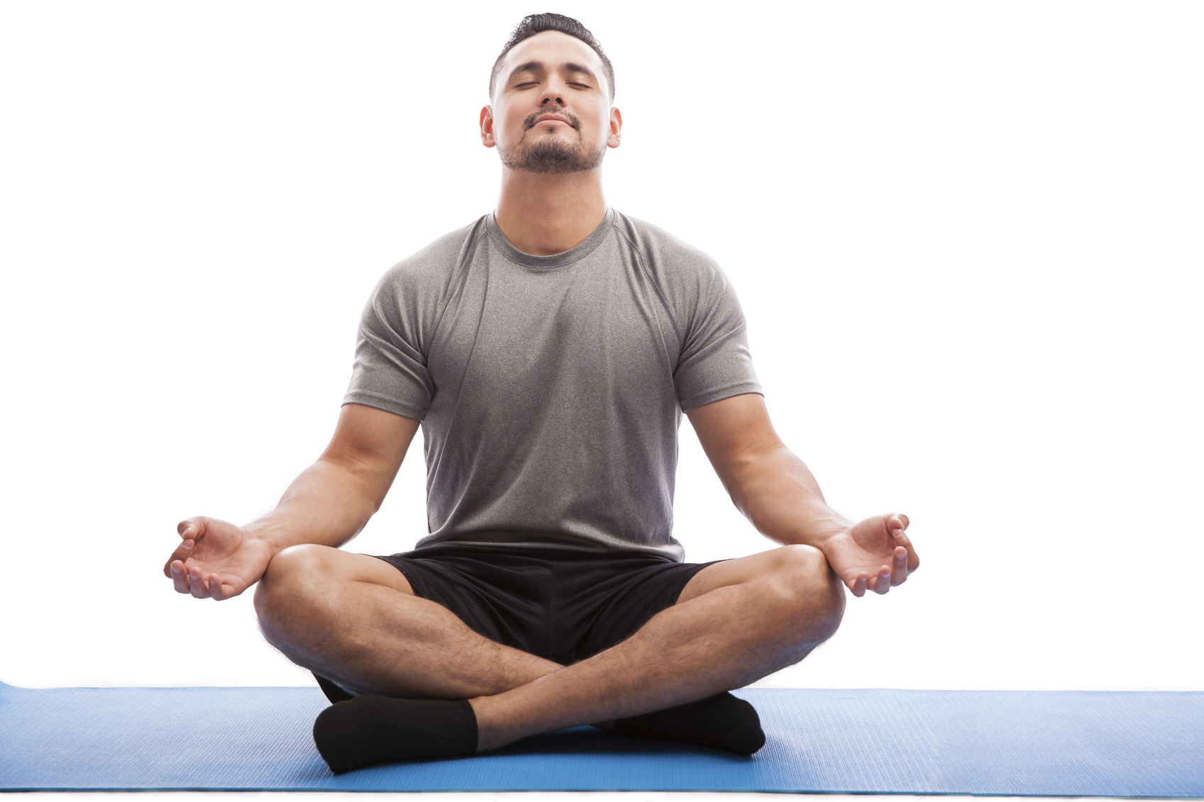 Young man in sporty outfit doing yoga and meditating on an exercise mat against a white background