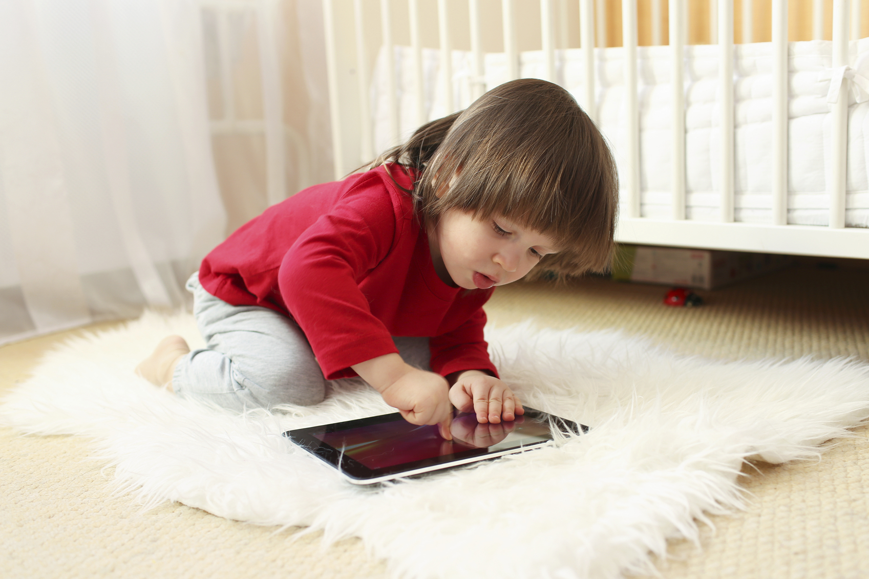 lovely 2 years boy in red shirt with tablet computer at home