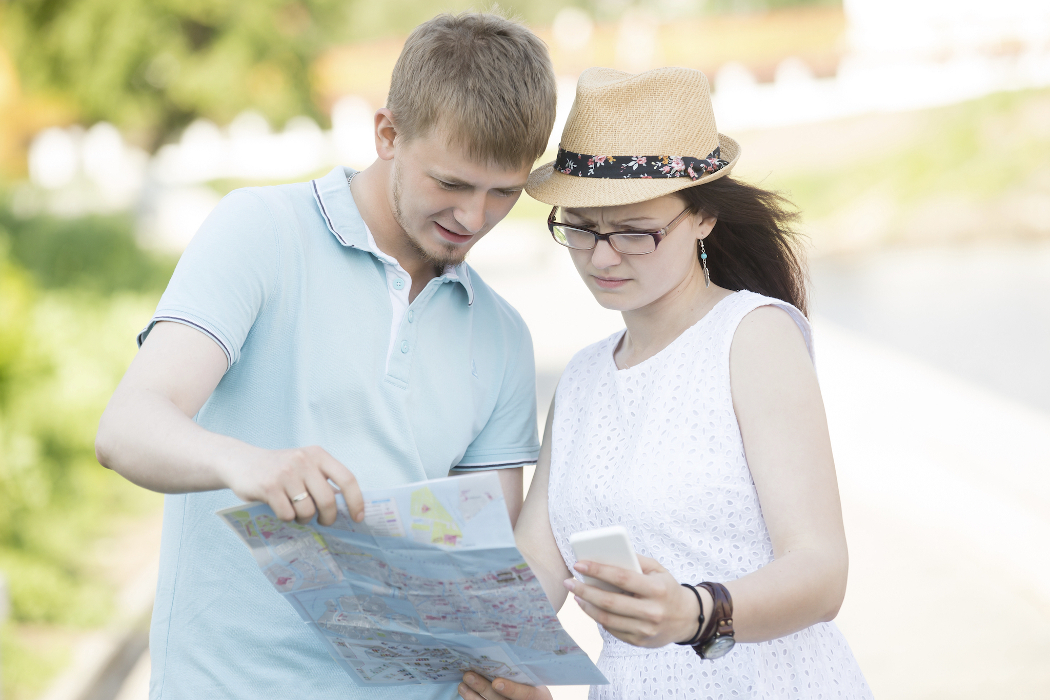 Beautiful traveling couple got lost and searching location on map. Man in blue t-shirt looking at map on summer trip. Woman wearing white dress, hat and glasses holding smartphone and frowning