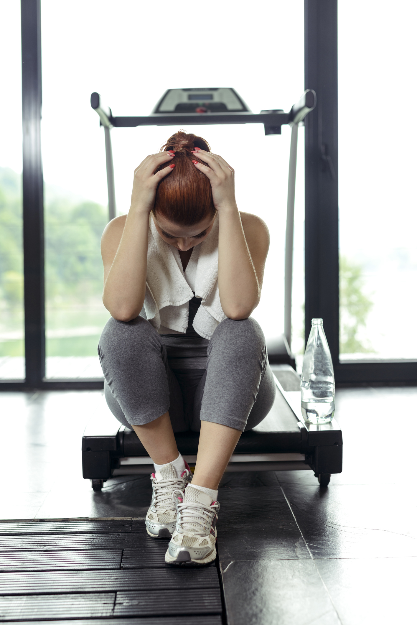 woman being tired after sport sitting on treadmill.
