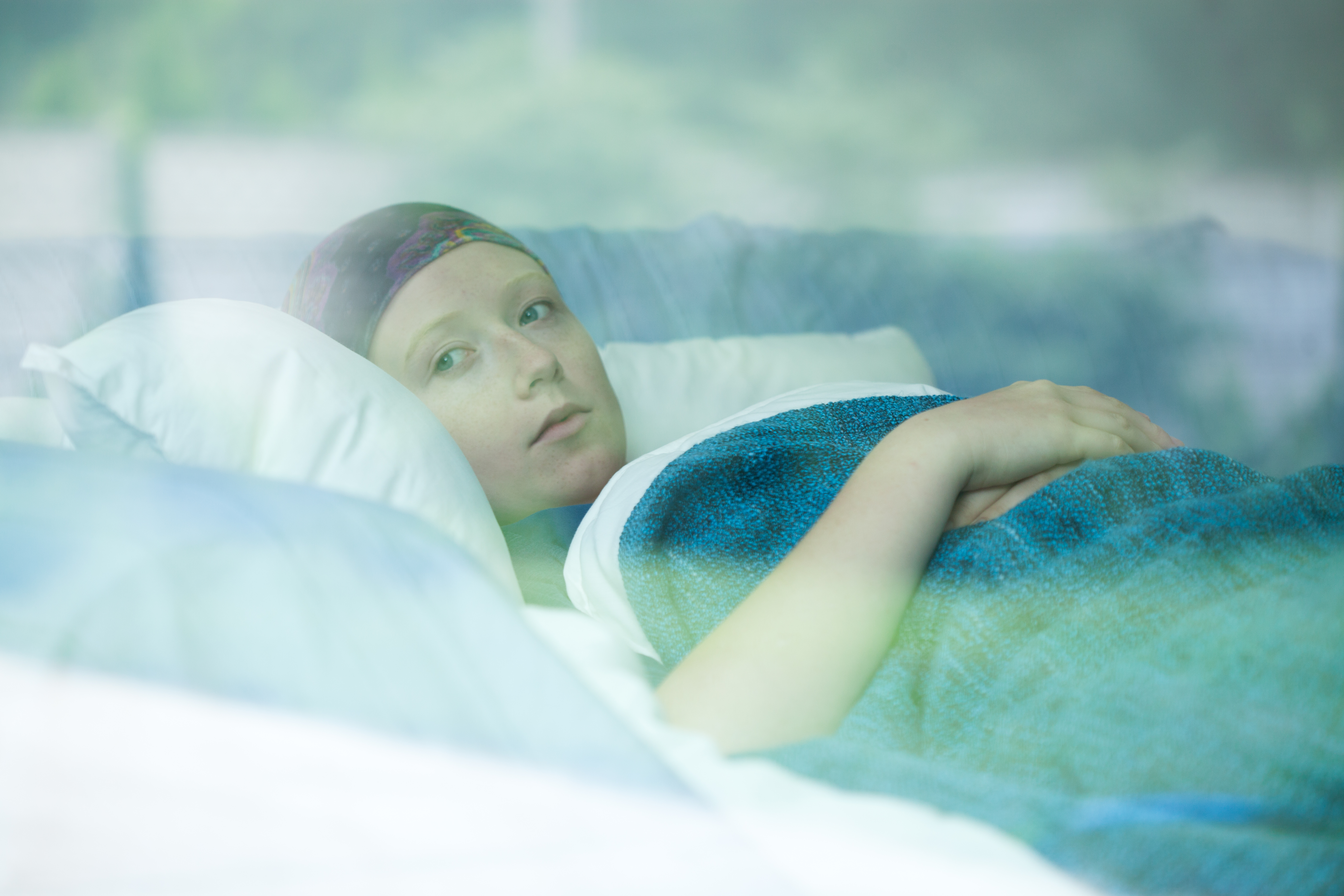 Young woman in bed suffering from cancer