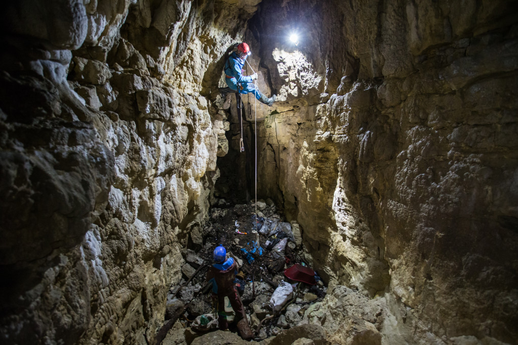 Speleologists clean out a subterranean cave from decades old wastes in Baudichonne near La Rippe, Switzerland, August 24, 2017. ©Pierre Albouy