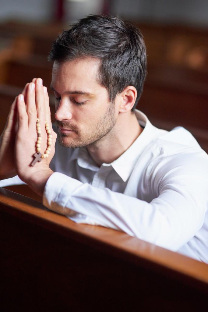Shot of a young man praying in a church